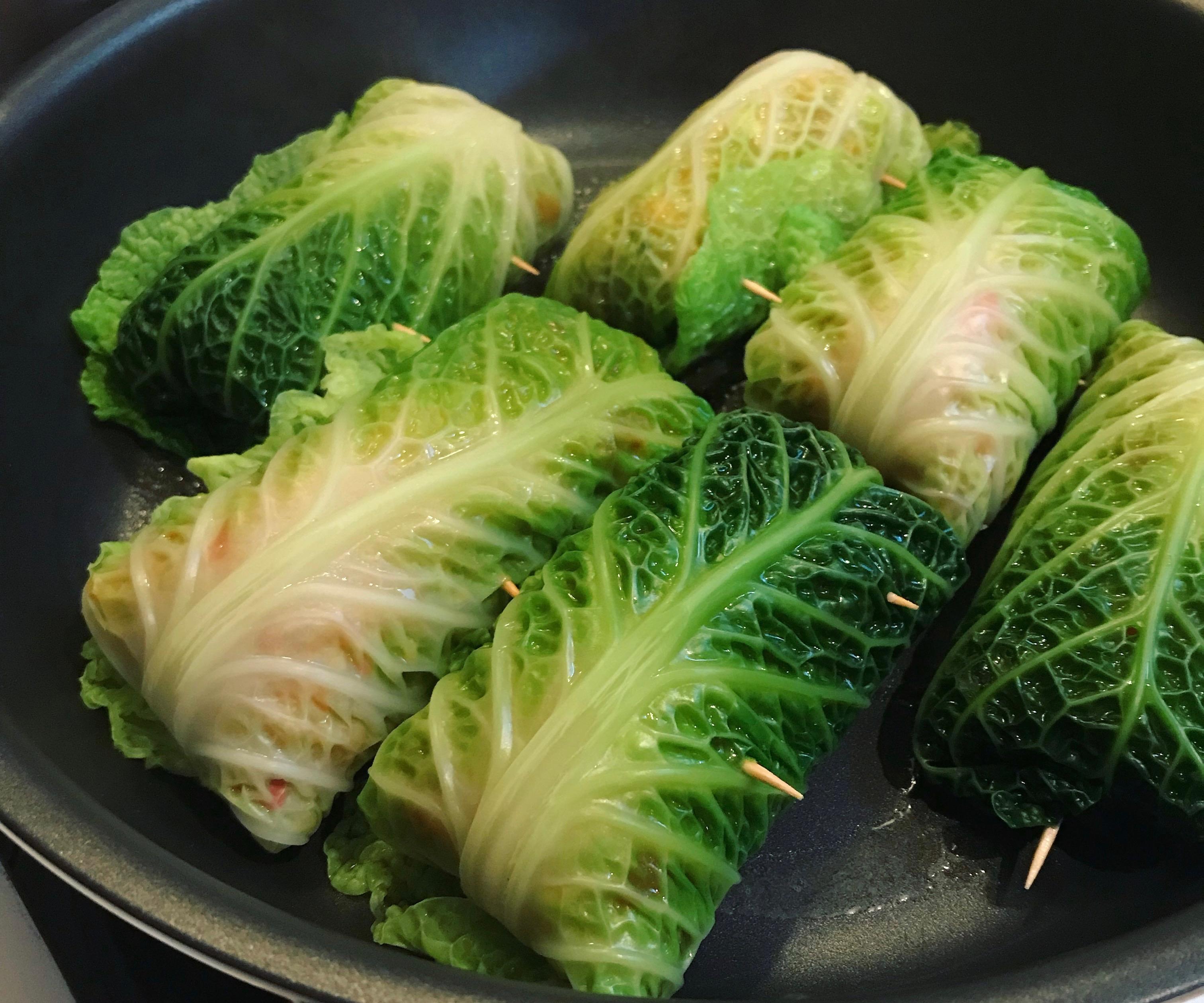 Die fertig gewickelten veganen Wirsingrouladen können zum Schluss noch in der Pfanne schmoren.